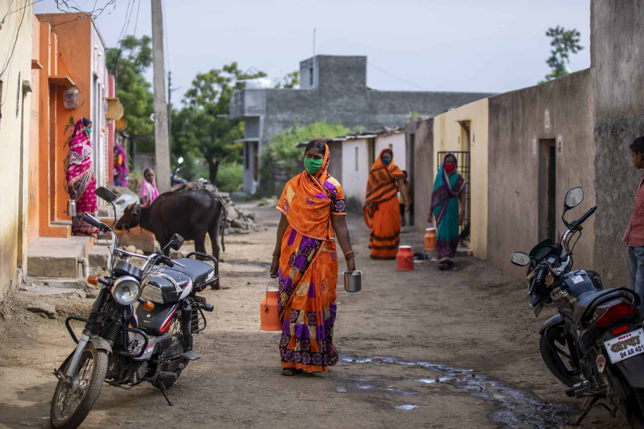 Indian dairy farmers delivering milk in street