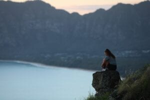 Woman sitting on a rock looking out at lake and mountains