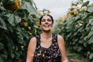 Woman laughing in garden with yellow petals falling around her.