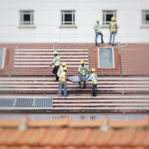 builders installing solar panels to a roof